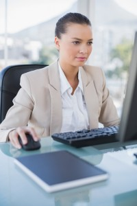 Concentrated businesswoman working on computer in bright office