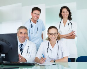 Medical team comprising male and female doctors posing together in an office smiling at the camera
